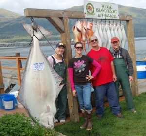 Jan, Shelby and Bob Arnold are shown with prospective family addition Justin rogers by Bob's lodge record halibut.